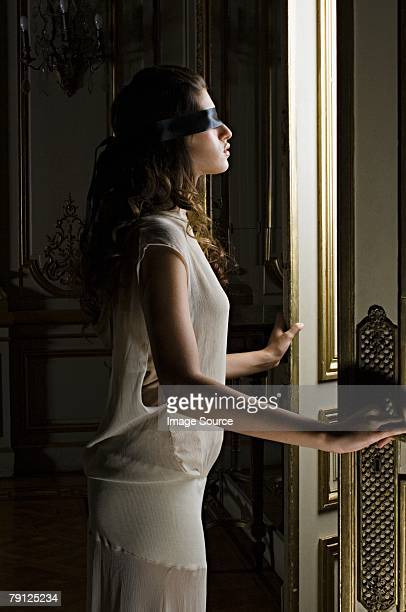 Blindfolded woman opening a door