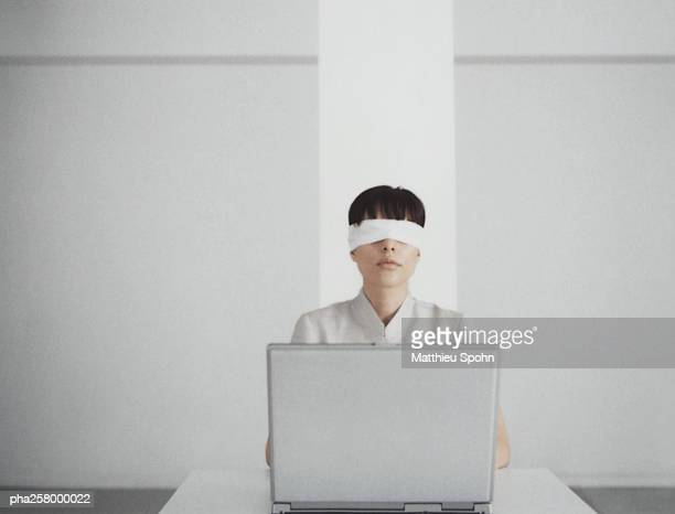 Blindfolded woman sitting behind laptop