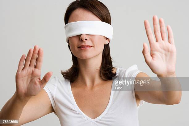 Blindfolded Woman with Arms Raised