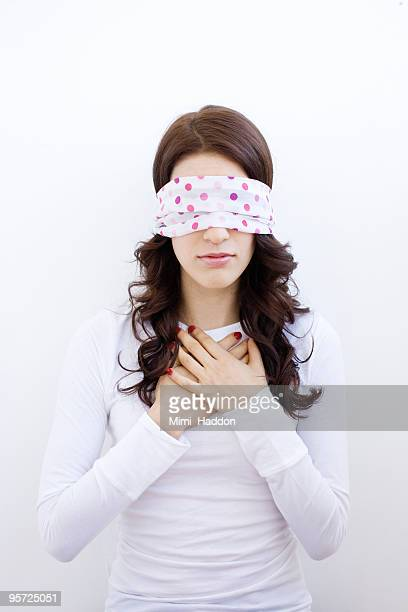 Blindfolded Woman with Hands on Chest