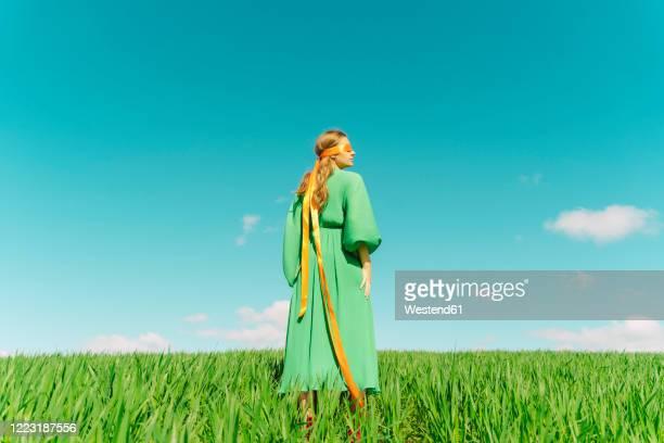 blindfolded young woman wearing a green dress standing in a field - grünes kleid stock-fotos und bilder
