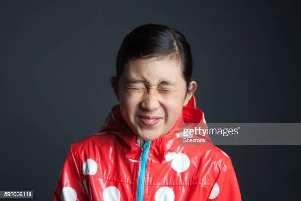 Blinking Asian girl wearing raincoat