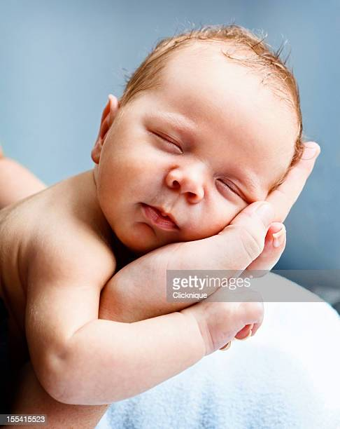 blissfully sleeping baby cradled in mothers hands - beginnings stock pictures, royalty-free photos & images