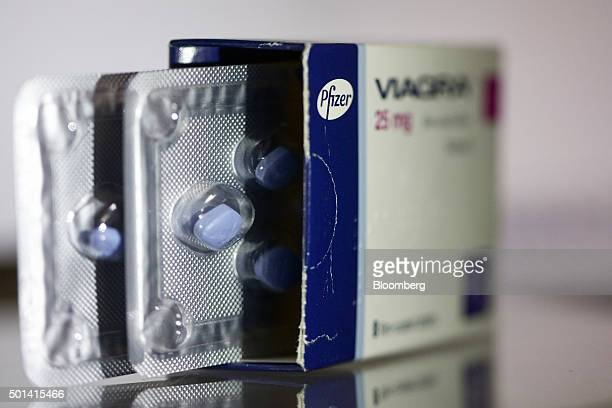 A blister pack containing Viagra tablets produced by Pfizer Inc sit inside a packet on a pharmacy counter in this arranged photograph in London UK on...
