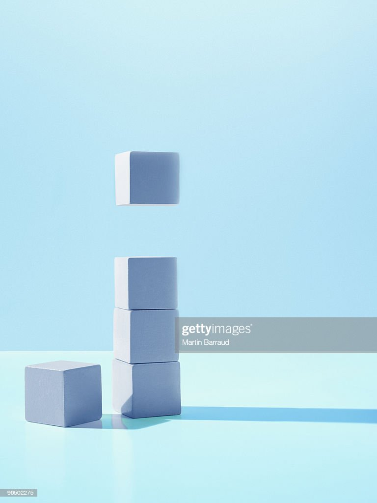Block hovering over stack of blocks : Stock Photo