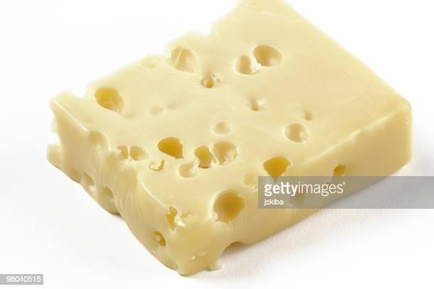 block of swiss cheese on a white background - zwitserse kaas stockfoto's en -beelden