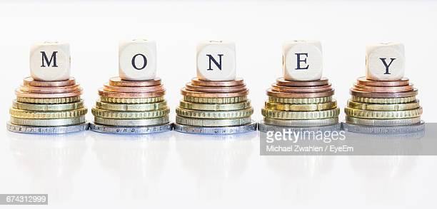 Block Shape Letters On Coins Against White Background