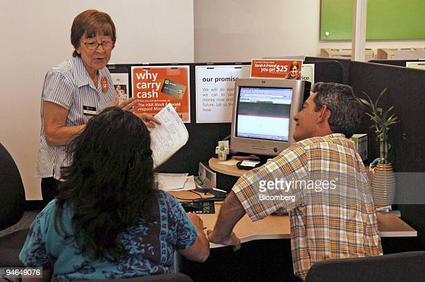 Block tax specialist Maria Rojas finishes her work with Patricia and George Protich at a branch office of the tax preparer's in Davie Florida Friday...