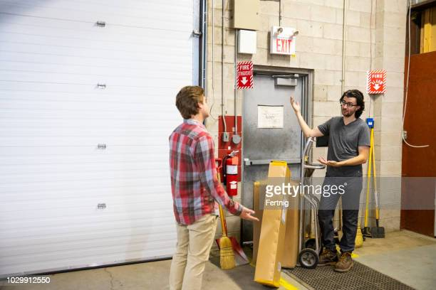 a blocked fire exit door in a warehouse. a supervisor is explaining the dangers of blocking an emergency exit to a new employee. - exit sign stock pictures, royalty-free photos & images