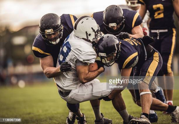 blocking an offensive player! - football player stock pictures, royalty-free photos & images