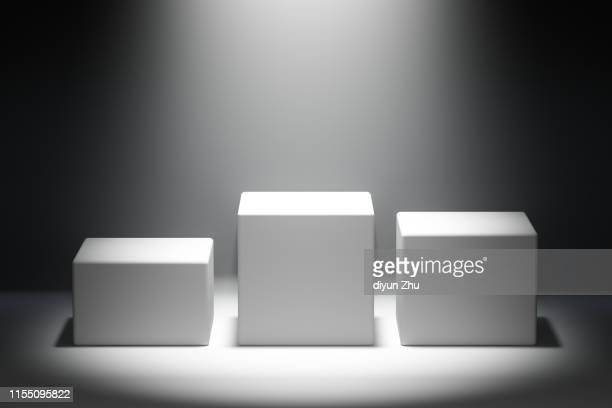 blocks of white podium with spotlight - winners podium stock pictures, royalty-free photos & images