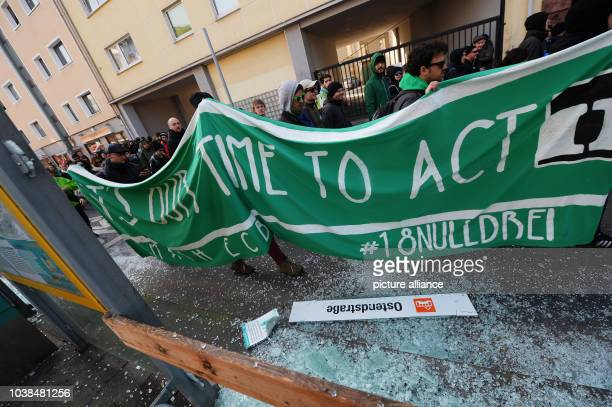 Blockupy activists walk past destroyed glass windows at the tram stop 'Ostendstrasse' during to the opening of the new European Central Bank...
