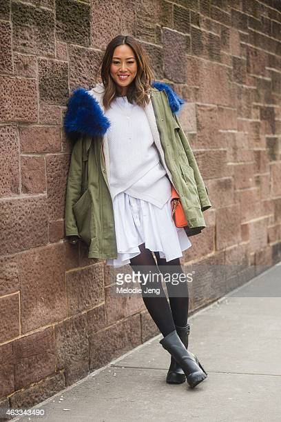 Blogger Aimee Song of Song of Style wears a Marissa Webb sweater and dress shirt Chloe clutch and Hunter boots at Streets of Manhattan on February 12...