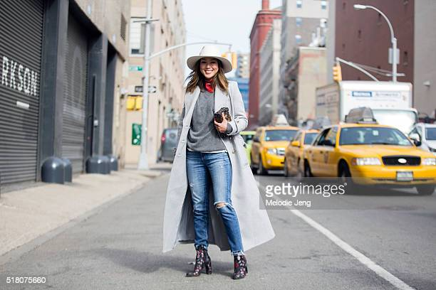 Blogger Aimee Song wears a gray Zimmermann coat a white hat red bandana around her neck gray sweater jeans Louis Vuitton Petite Malle purse and...