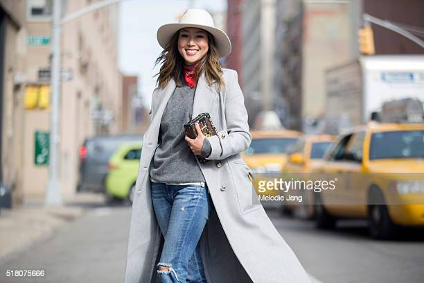 Blogger Aimee Song wears a gray Zimmermann coat a white hat red bandana around her neck gray sweater jeans and a Louis Vuitton Petite Malle purse at...