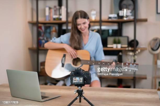 blogger live broadcasting music instrument tutorial on social media. vlogger recording online vlog video. influencer marketing - live broadcast stock pictures, royalty-free photos & images