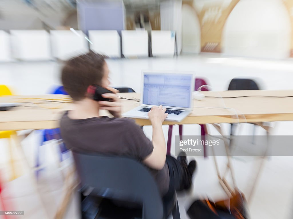 Blogger using a laptop and a cell phone : Stock Photo