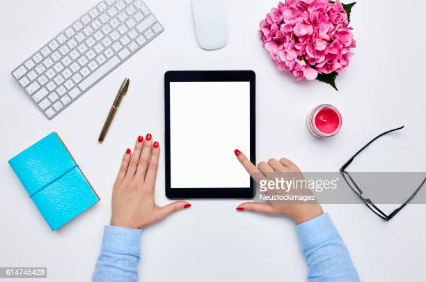 blogger using digital tablet by desk supplies against white back - red nail polish stock pictures, royalty-free photos & images