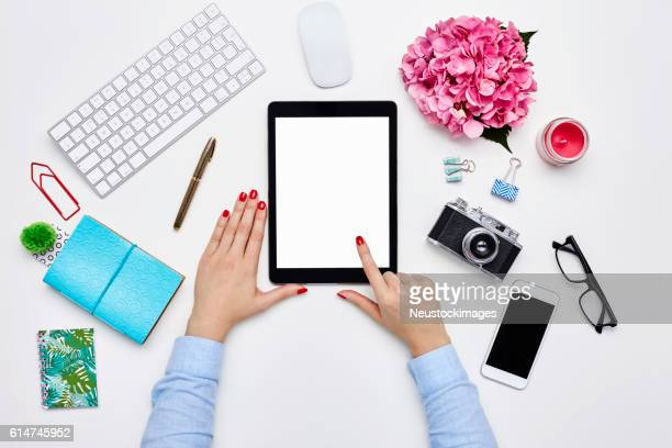 Blogger using digital tablet by desk supplies on white backgroun