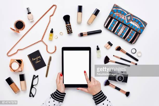 blogger using digital tablet surrounded with beauty products - pochette borsetta foto e immagini stock