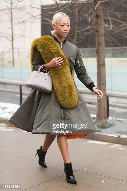 Blogger Vanessa Hong wears a The Haute Pursuit fur piece a Pixie Market jacket Prada bag and Stuart Weitzman heels at Streets of Manhattan on...