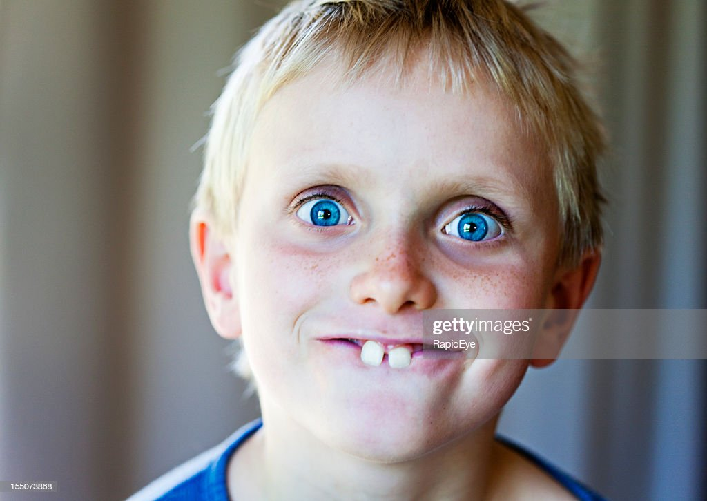 Blond 8 year old boy makes funny Bugs Bunny face : Stock Photo