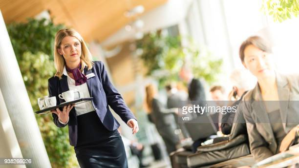 Blond airport waitress carrying tray with coffee