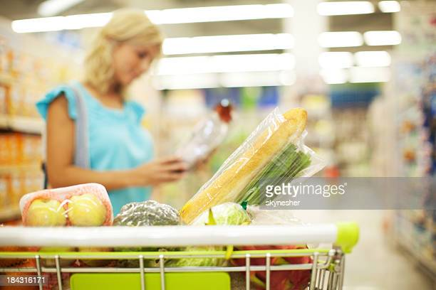 blond attractive woman buying groceries in supermarket. - labeling stock photos and pictures