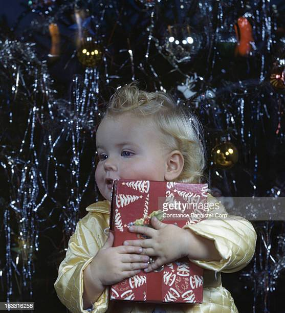 Blond baby girl holding gift in front of Christmas tree New York City