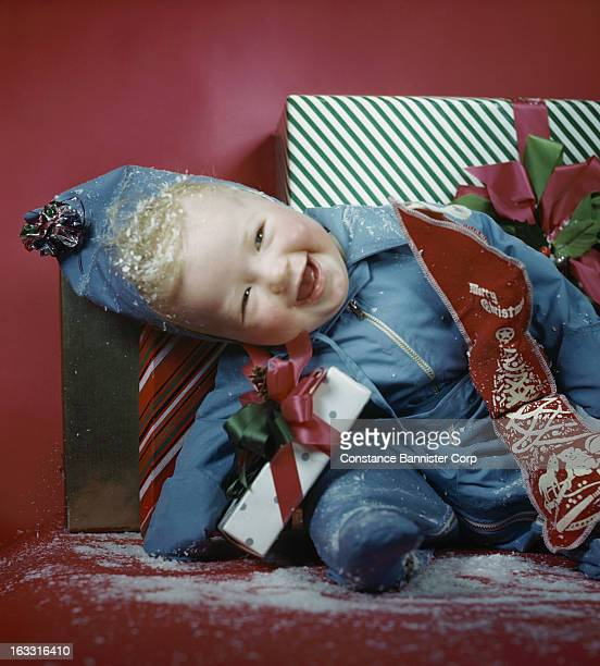 Blond baby sitting wearing blue snow suit with head tilted holding a Christmas stocking New York City USA