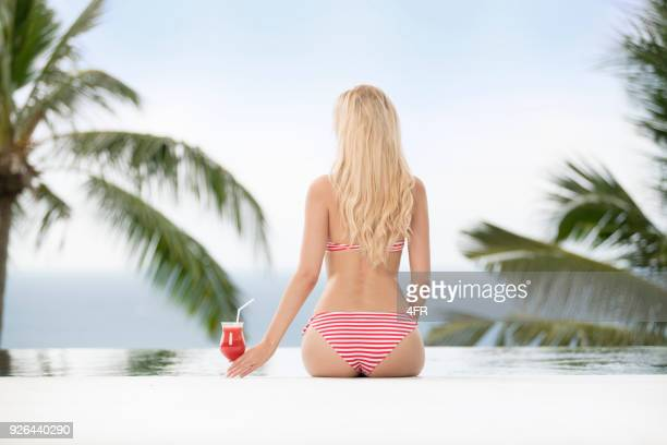 Blond Bikini Beauty with Cocktail by the Pool on Vacation