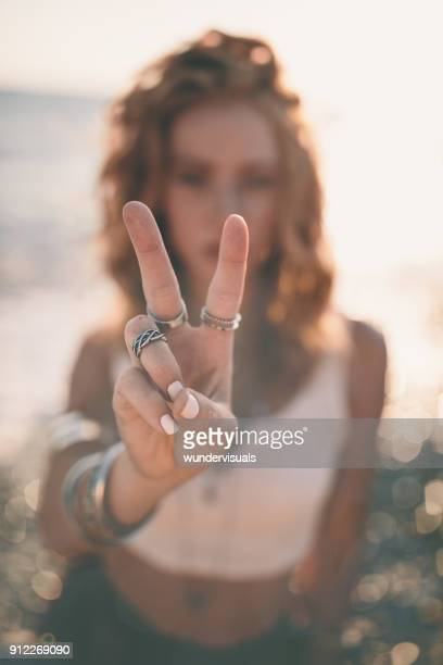 blond bohemian woman making a peace sign at the beach - symbol stock pictures, royalty-free photos & images