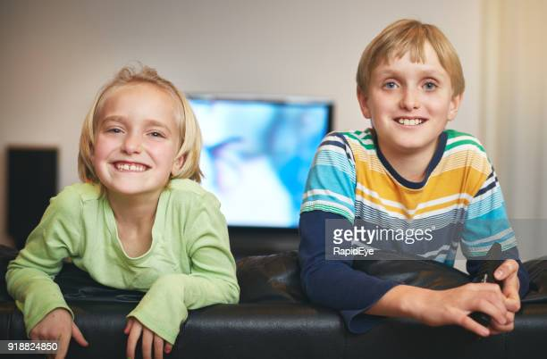 Blond boy and girl look over back of couch,  smiling