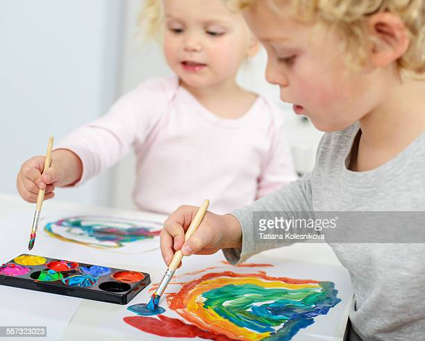 A blond boy and his younger sister are painting