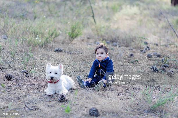 Blond boy and westy sitting in a forest