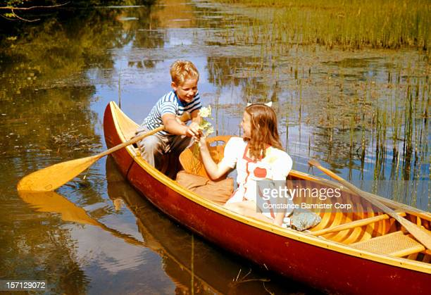 A blond boy gives a flower to a girl in a canoe Palm Beach Florida 1947