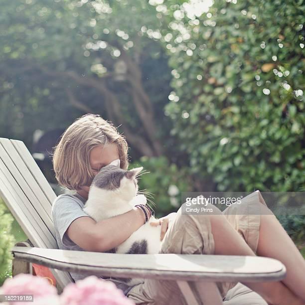 Blond boy in a garden chair cuddling his cat