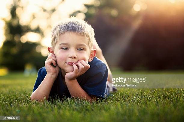 Blond boy lying on grass at sunset