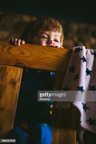Blond Boy Sitting On Bed