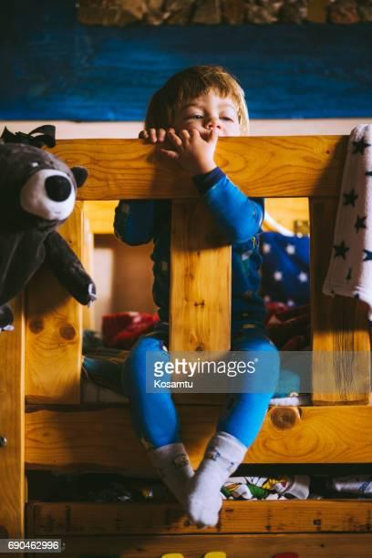 Blond Boy Sitting On Bunk Bed