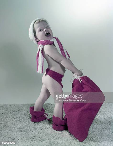 Blond boy wearing cap scarf and botties holding red bag of presents Bare Bottom