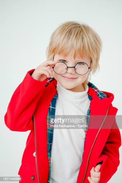 blond boy with glasses. a beautiful blonde child. boy in a red coat. - coat stock pictures, royalty-free photos & images