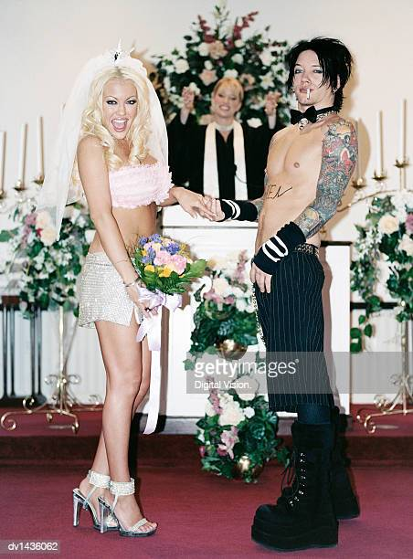 blond bride and a half-dressed punk groom getting married in a church - ceremonia matrimonial fotografías e imágenes de stock