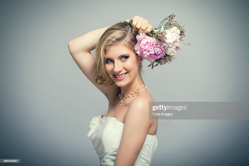 Blond bride holding bouquet of pink flowers : Stock Photo