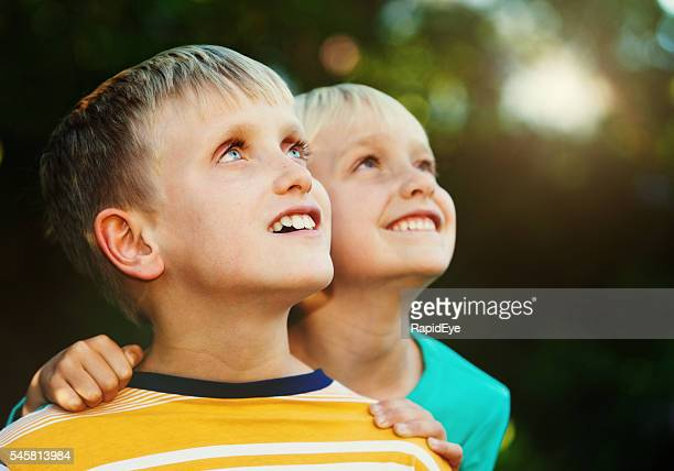 blond brother and sister looking up smiling, amazed and delighted - religion stock-fotos und bilder