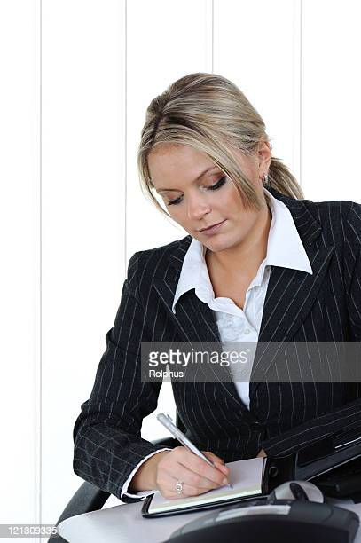 blond business woman writing in planner office - black blouse stock pictures, royalty-free photos & images