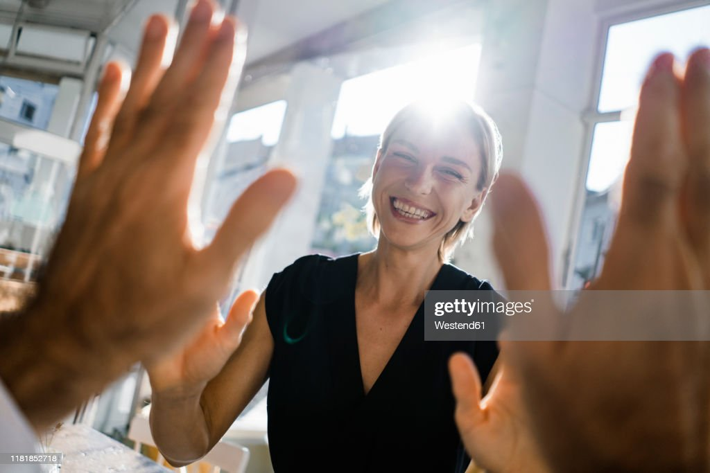 Blond businesswoman high fiving a colleague : Stock-Foto