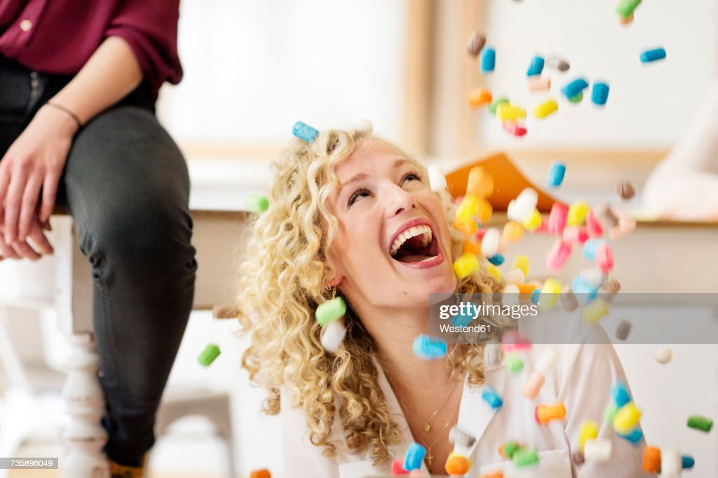 Blond businesswoman laughing about falling marshmellows : Stock Photo