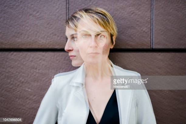 Blond businesswoman leaning against wall, dopple exposure