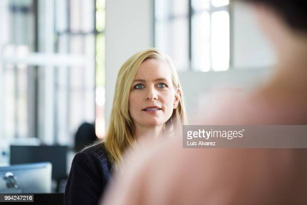 blond businesswoman looking at female colleague - variable schärfentiefe stock-fotos und bilder